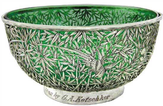 """竹叶纹镂空琉璃大碗   Glass bowl with Openwork Silver Base with Bamboo Leaf Design   晚清 通高:10.6cm;口径:20.6cm;底径:11.5cm;银托重:463g;琉璃重:806g 款识:怡安,WH,90   收藏界素有""""货高一等,价高十倍""""的说法,晚清是中国外销银器种类最多、数量最丰富的时期,激烈的竞争使银匠在工艺和设计上都下足功夫,创造出各种精品。这件竹叶纹镂空琉璃大碗镶边,弧壁,深腹,圈足,运用镂空工艺通体镂雕竹林,在其中还镂雕一鸟穿梭于林间,碗底镂空形成钱币纹样,寓意财源广进。此碗工艺固然精湛,但银匠的创造力更让人赞叹,在内部配以一绿色琉璃碗,结合银碗的竹林造型产生绿影流动、生机盎然之感,令人赏心悦目。巧妙的搭配也使得这件银碗成为了同种器物中不可多得的精品。"""
