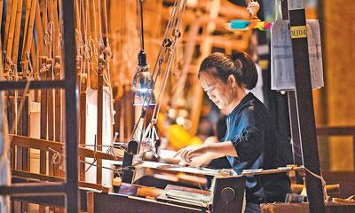 在江苏南京云锦博物馆,一名织工在编织云锦。