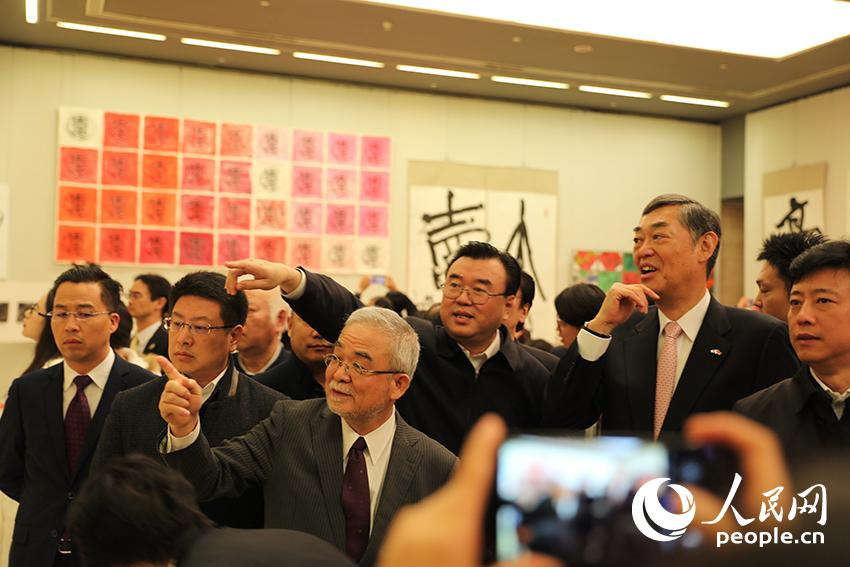 师村妙石向来宾解说正在展出的篆刻作品。