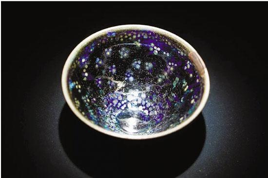 宋 曜变天目建盏(1951年定为日本国宝) 口径: 12.2cm 高度: 6.4cm 藏于大德寺龙光院 束口、深腹,釉斑随着光线变化色泽,黑斑点外套着蓝紫色光环,具有幽玄之美。据传这件曜变在明朝传到日本,是龙光院的创建者江月宗玩所有,1606年被视为镇院之宝,作为佛器供奉。