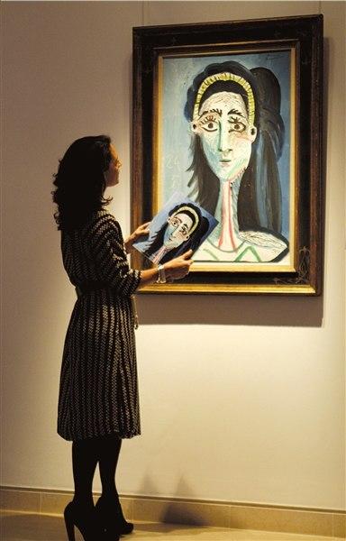 工作人员欣赏毕加索的画作《女人头像(杰奎琳)》。(来源:京华时报)